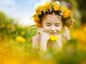 Little girl wearing dandelion wreath lying on flower meadow and smiling