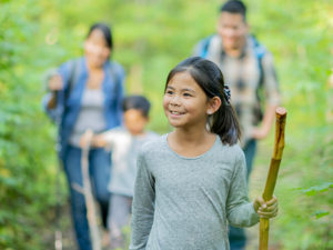 A girl holding a walking stick is leading her family through a forest adventure.