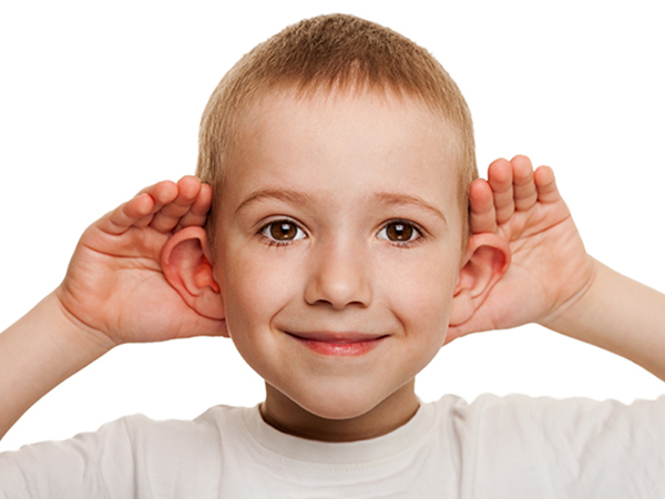 Young smiling boy with his hands on ears listening.