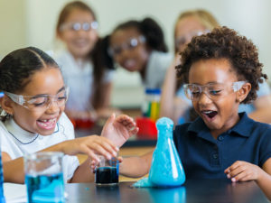 Young kids excited as foam overflows from beaker during chemistry experiment.